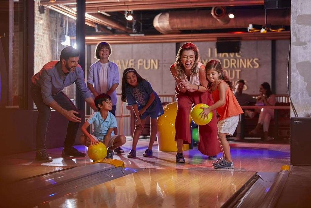 Family enjoying bowling together at playing area